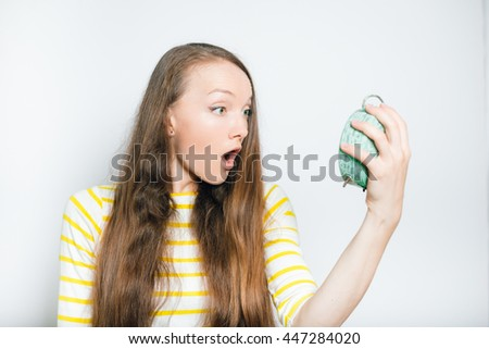 beautiful young woman looking frightened at the alarm clock, isolated on a gray background - stock photo
