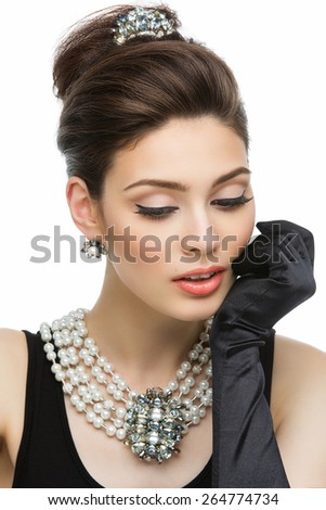 Beautiful young woman looking like Audrey Hepburn wearing pearls - stock photo