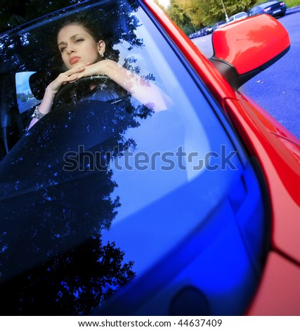 beautiful young woman looking through a car windshield