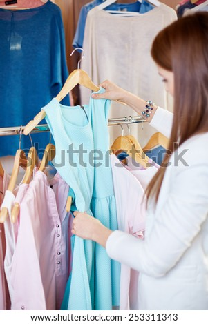 Beautiful young woman looking through new clothes collection