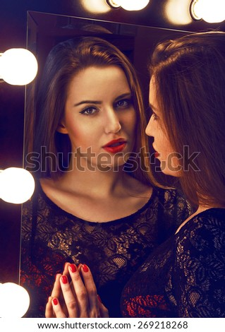 Beautiful young woman looking to the camera through the big mirror with the lights.   Developed from RAW. Retouched with special care and attention. - stock photo