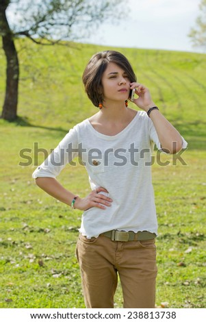 Beautiful young woman looks annoyed while talking on the phone - stock photo