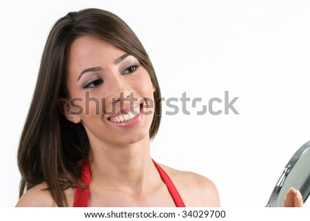 Beautiful young woman looks at her face in the mirror - stock photo