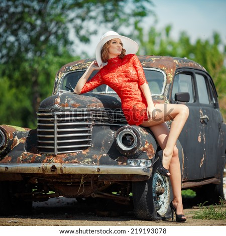 Beautiful young woman looks sexy, comes against the backdrop of an old black car in a red dress. Girl in red dress holding a white hat. Image of a woman who looks away. - stock photo
