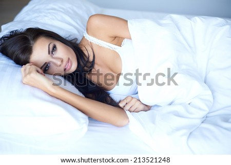 Beautiful young woman lying awake in bed thinking with a serious expression as she struggles to get to sleep with insomnia