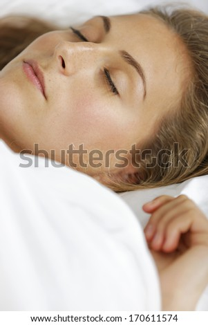 Beautiful young woman lying in bed.