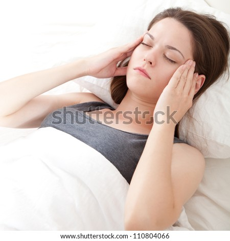 Beautiful young woman lying in bed and having migraine