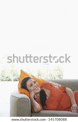 Beautiful young woman lying in sofa while looking away and smiling