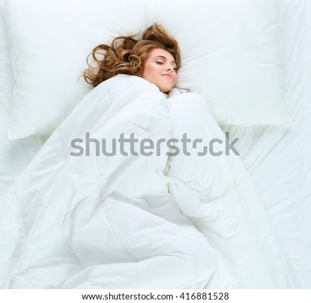 Beautiful young woman lying on bed - stock photo