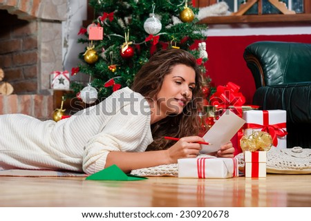 Beautiful young woman lying on carpet with a red pen writing a christmas card / Christmas presents in front of tree over living room - stock photo