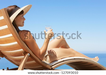 Beautiful young woman lying on deckchair - stock photo