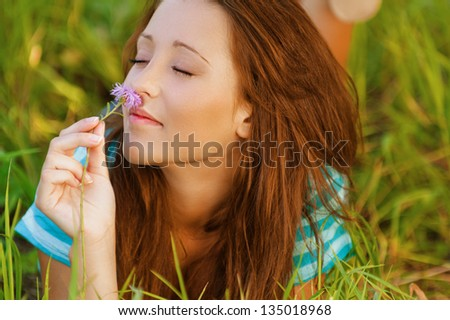 Beautiful young woman lying on grass and smelling flower, against background of summer green park. - stock photo