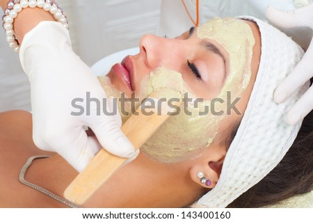 Beautiful young woman lying on massage table while natural facial mask is applied on her face. - stock photo