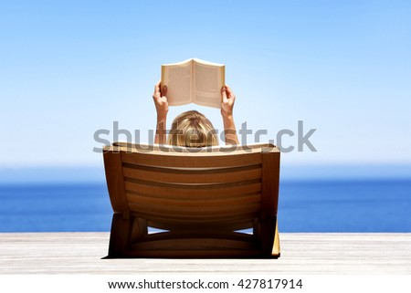 beautiful young woman lying on sand near the sea and reading - stock photo