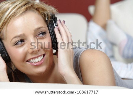 Beautiful young woman lying on sofa at home listening to music on headphones