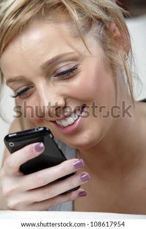 Beautiful young woman lying on sofa at home reading a text message. - stock photo