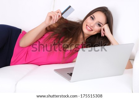 Beautiful young woman lying on sofa  with laptop on white background