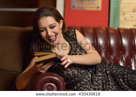 Beautiful young woman lying on the couch reading a book
