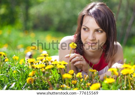 Beautiful young woman lying on the field of dandelions - stock photo