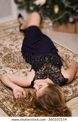 Beautiful young woman lying on the floor in boudoir