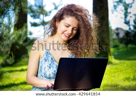 Beautiful young woman lying on the grass and working with a laptop