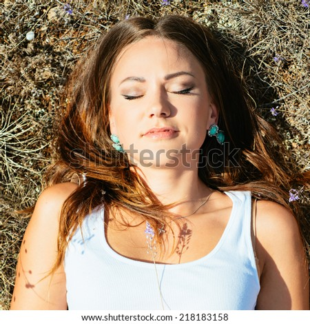 Beautiful young woman lying on the grass enjoying summer sun. Photo with instagram style filters - stock photo