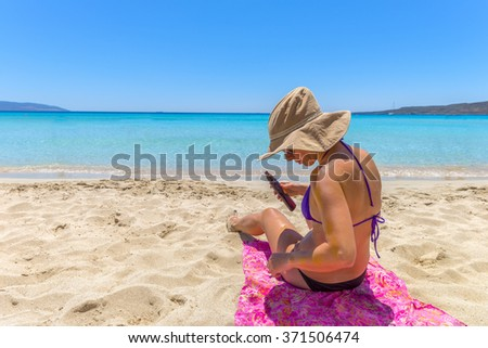 Beautiful young woman lying on the magnificent beach of Elafonisi, Crete, Greece, one of the most beautiful beaches in the world.
