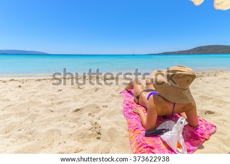 Beautiful young woman lying on the magnificent beach of Elafonisi, Crete, Greece, one of the most beautiful beaches in the world. - stock photo