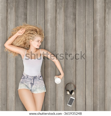 Beautiful young woman lying on the wooden floor with music headphones, smartphone and a take away coffee cup; view from above. - stock photo