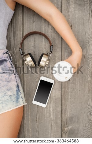 Beautiful young woman lying on the wooden floor with music headphones, smartphone and a take away coffee cup; view from above.