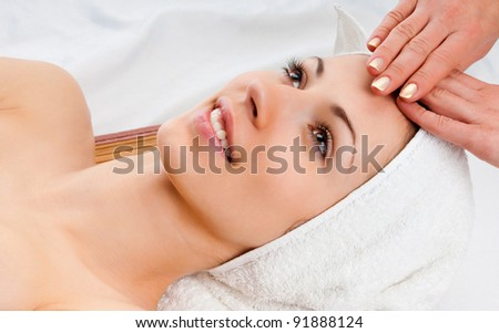 beautiful young woman lying relaxed in a spa salon and receiving facial massage - stock photo