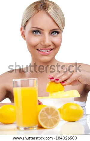 Beautiful young woman making fresh lemonade - stock photo