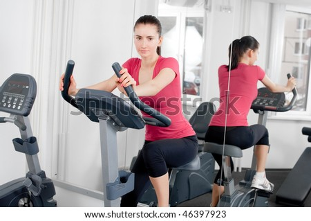 beautiful young woman making her exercises on an exercise bicycle
