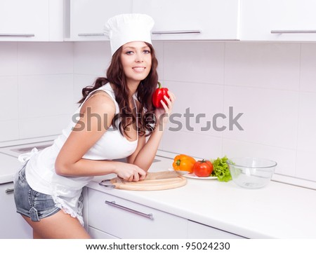 beautiful young woman making salad of vegetables in the kitchen at home