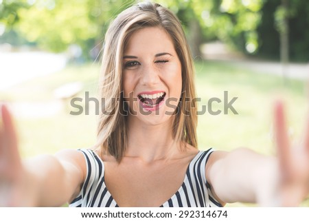 Beautiful young woman making selfie and grimacing - stock photo