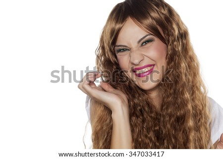 beautiful young woman making ugly face on a white background
