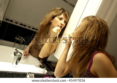 Beautiful Young Woman Making Up with Lip Liner in front of the Dresser