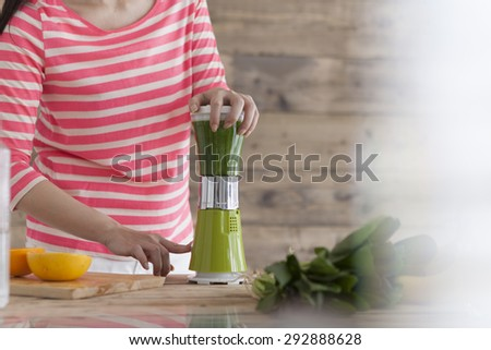 Beautiful Young Woman Making vegetables Smoothie in blender - stock photo