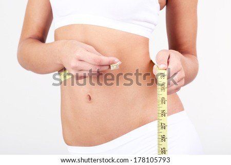 Beautiful young woman measuring her body with tape on grey background