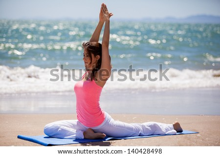 Beautiful young woman meditating and doing some yoga at the beach - stock photo