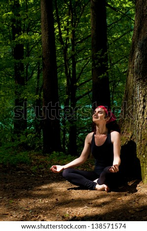 Beautiful young woman meditating in forest - stock photo