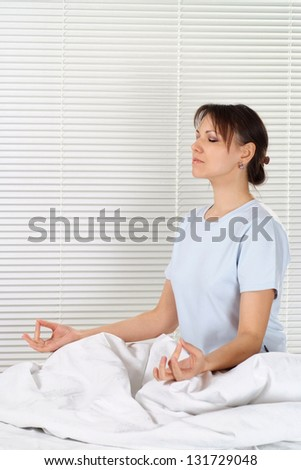 Beautiful young woman meditating in the morning - stock photo