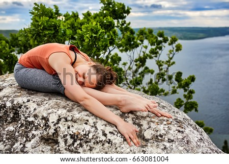 Beautiful young woman meditating in yoga pose at a big river against dramatic sky.