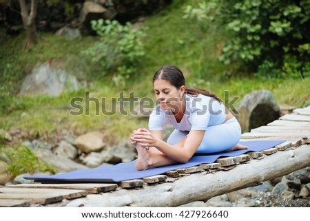 Beautiful young woman meditating in yoga pose at a mountain stream. Selective focus on woman. - stock photo