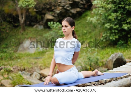 Beautiful young woman meditating in yoga pose at a wild mountain stream.  - stock photo