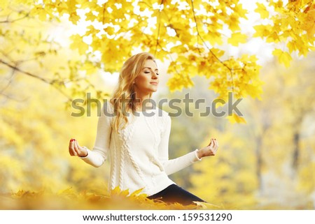 Beautiful young woman meditating outdoors in autumn park - stock photo