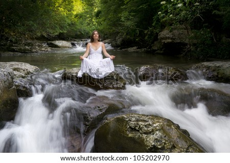 Beautiful young woman meditating surrounded by the purifying waters of a clear mountain stream