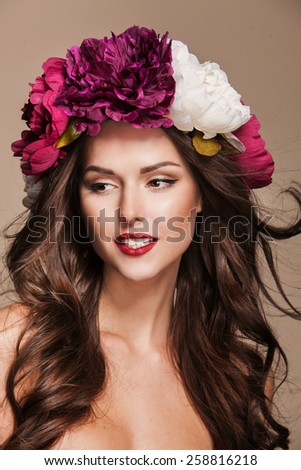 beautiful young woman model with bright flowers on her head