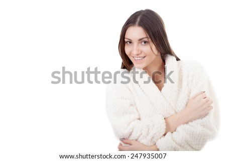 Beautiful young woman muffle, wrap herself up in white bathrobe, isolated, white background. Cozy, comfort, wellbeing, healthcare, bodycare concepts