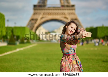 Beautiful young woman near the Eiffel tower in Paris taking selfie with her mobile phone - stock photo